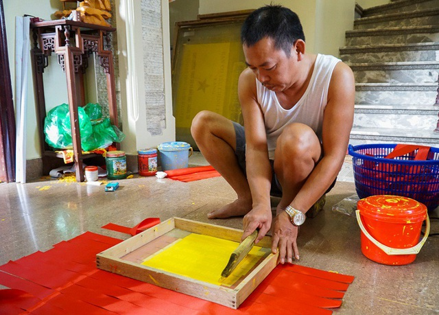 """Những tấm băng rôn sau khi lấy ra từ máy cắt sẽ được dập khuôn in chữ """"Việt Nam vô địch""""."""
