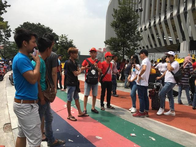 Bạn Trần Văn Hoàng (áo đỏ bên phải) bức xúc vì không mua được vé vào sân trận đấu ngày mai - Ảnh: Trọng Trinh