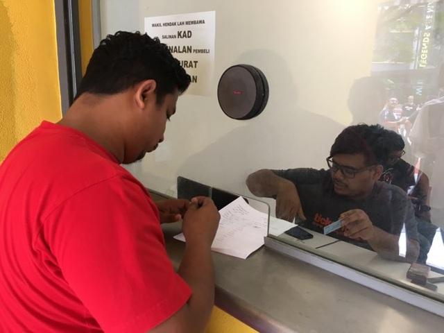 Cổ động viên Malaysia nhận vé online ở bên ngoài sân Bukit Jalil - Ảnh: Trọng Trinh