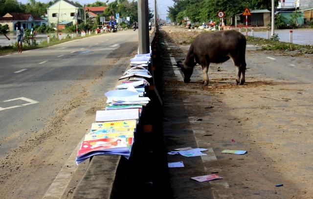 Người dân mang đồ đạc, sách vở bị ngập lụt ra ngoài quốc lộ 1 phơi sau khi nước rút