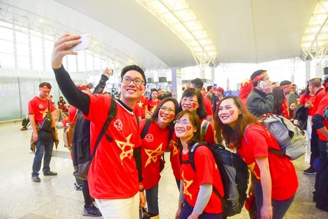 Một nhóm cổ động viên tranh thủ chụp ảnh tự sướng trước giờ lên máy bay.