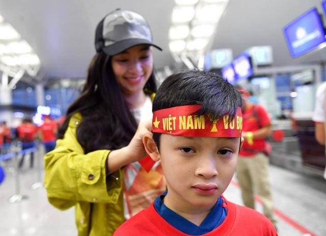 Một cổ động viên nhí đeo băng rôn có dòng chữ Việt Nam vô địch.
