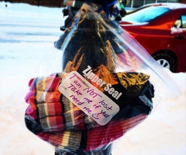 """Những chiếc mũ, khăn len được một nhà hảo tâm bí ẩn treo khắp thành phố để trợ giúp người có hoàn cảnh khó khăn, vào ngày trời trở rét (chữ trên chiếc túi: """"tôi không phải bị thất lạc, hãy lấy nếu bạn cảm thấy cần"""")."""