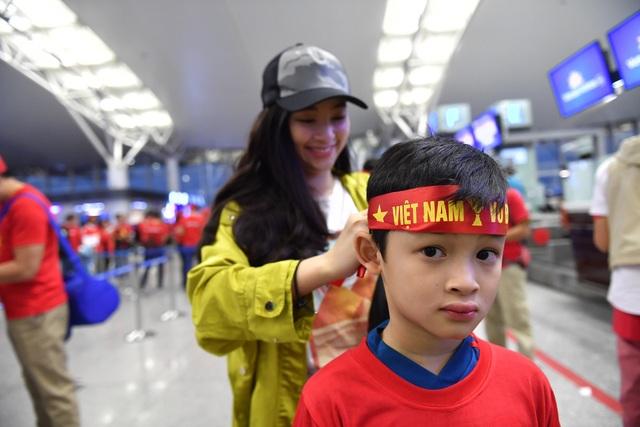 Trong đoàn người đi cổ vũ đội tuyển Việt Nam có cả những cổ động viên nhí. Trong ảnh là em Minh Anh (8 tuổi, Hà Nội) đang được người thân đeo băng rôn tiếp lửa cho đội nhà trước khi sang Malaysia.