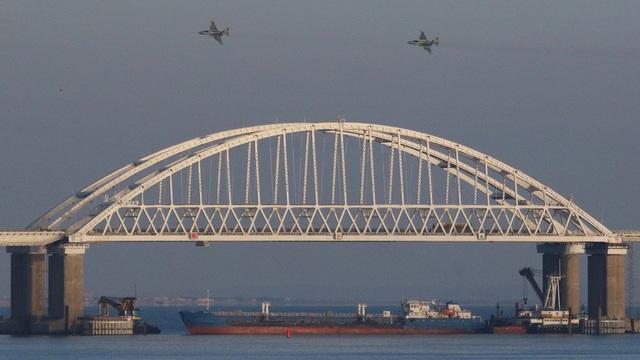 Tàu chở hàng Nga chặn lối ra vào dưới cầu tại eo biển Kerch trong khi máy bay hoạt động trên không trong vụ đụng độ với các tàu Ukraine hôm 25/11. (Ảnh: TASS)