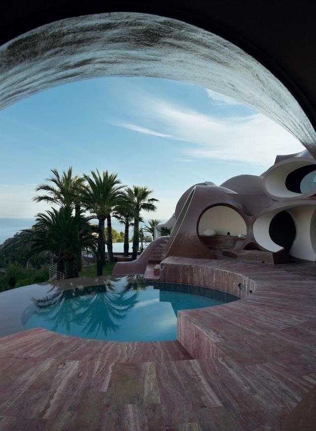 """""""Palais Bulles"""" là một ngôi nhà được thiết kể bởi kiến trúc sư người Hungary, Antti Lovag. Xây dựng vào năm 1989 – kỷ nguyên con người bắt đầu tiến ra ngoài vũ trụ - nên công trình này cũng mang một dáng vẻ rất """"ngoài hành tinh"""". Palais Bulles gần như không có một góc cạnh nào và khi nhìn từ xa, nó trông không khác gì những bong bóng kết lại với nhau. Được biết, chủ nhân nổi tiếng nhất của dinh thự độc đáo này chính là nhà thiết kế thời trang lừng danh Pierre Cardin."""