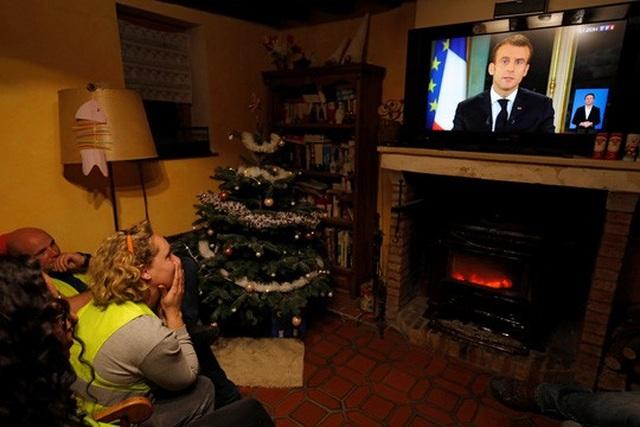 """Người biểu tình """"Áo ghi-lê vàng"""" nghe bài phát biểu của Tổng thống Pháp Emmanuel Macron trên truyền hình tại Gaillon hôm 10-12 Ảnh: REUTERS"""