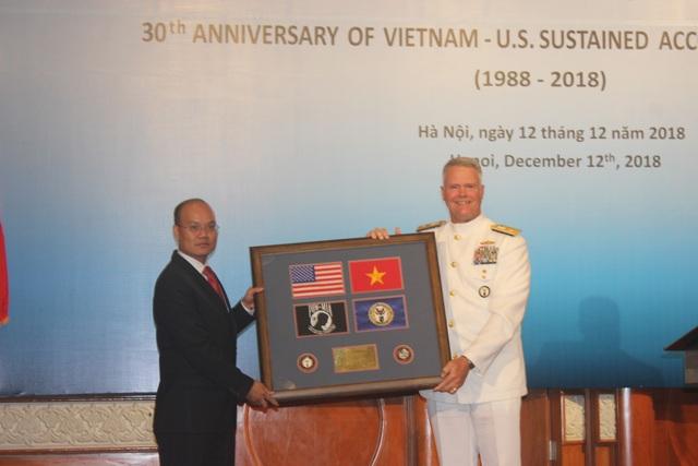 Chuẩn Đô đốc Jon Kreitz trao quà lưu niệm tại Lễ kỷ niệm 30 năm hợp tác về tìm kiếm người Mỹ mất tích trong chiến tranh. (Ảnh: Thành Đạt)
