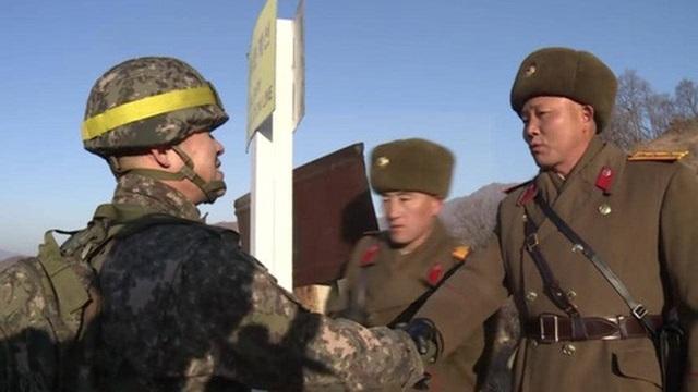 Binh sĩ liên Triều bắt tay nhau ở biên giới trước khi băng qua DMZ vào lãnh thổ của nhau. Ảnh: Herald Sun