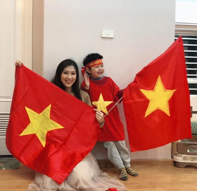 Mẹ con Hoa hậu Áo dài Phí Thuỳ Linh mặc áo cờ đỏ sao vàng, giơ cờ Tổ quốc cổ vũ cho đội nhà.