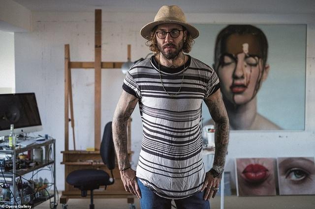 Họa sĩ Mike Dargas đứng bên những bức tranh của mình.