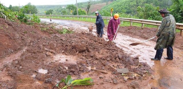 Cơ quan chức năng tiến hành dọn dẹp khu vực bị sạt lở gây cản trở giao thông (ảnh T.N)