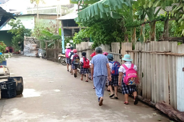 Dù ở tuổi 81, lưng đã còm nhưng bà Hai vẫn chưa thể bỏ nghề dẫn con nít đi học