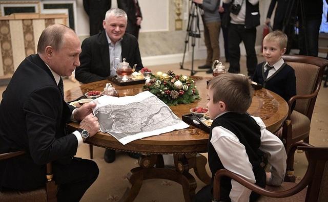 Ông Putin đã chỉ cho cậu bé lộ trình của chuyến bay mà Palyanov sẽ được nhận như một món quà năm mới của Tổng thống Nga.
