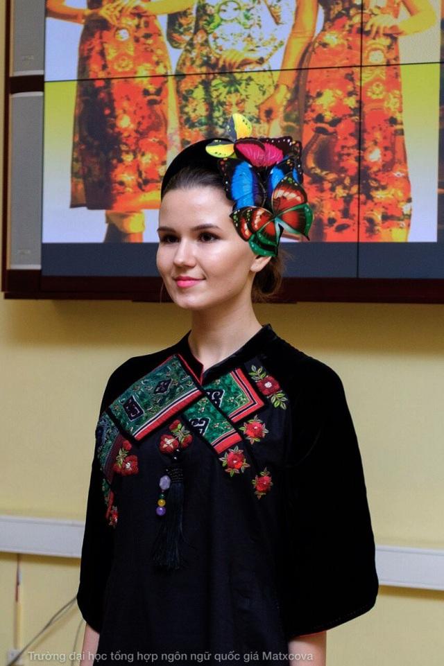 Một học sinh khoa tiếng Việt đang trình diễn áo dài thổ cẩm.