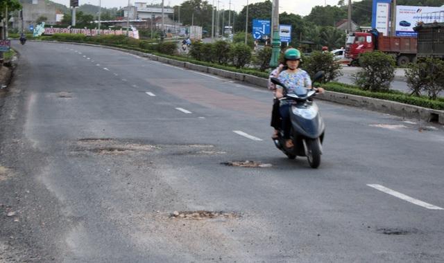 Một người lái xe máy vì né ổ gà mà tràn qua phần đường ô tô