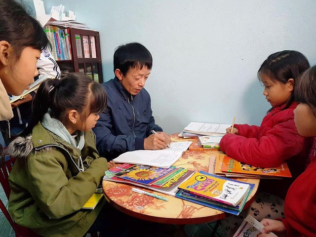 Thầy giáo làng Bùi Văn Đông hướng dẫn các em học sinh đọc sách.