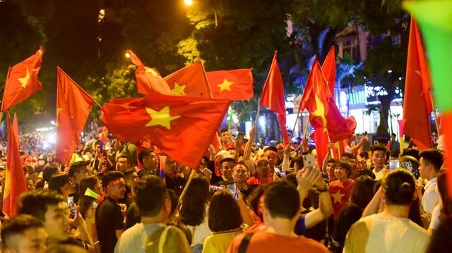 Mỗi người cầm trên tay một lá cờ tổ quốc hát Quốc ca.