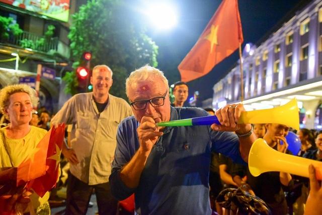 Người nước ngoài thổi kèn vuvuzela chúc mừng chiến thắng dội tuyển Việt Nam.