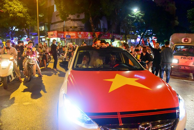 Chiếc ô tô được dán hình cờ đỏ sao vàng trước ca pô xe.