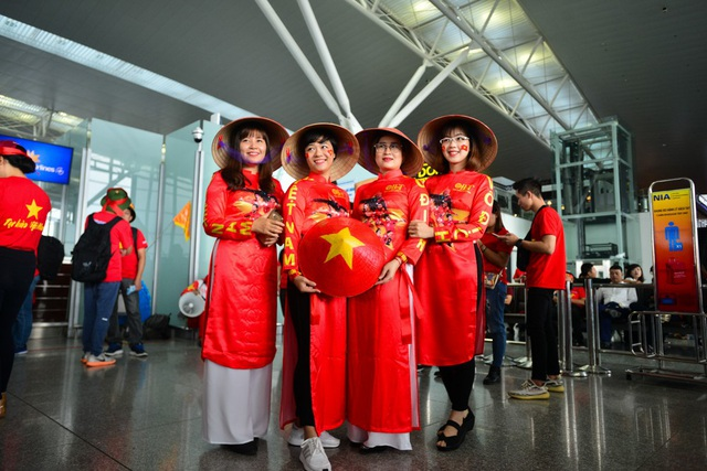 Một nhóm cổ động viên mặc trang phục áo dài đỏ cách tân có in dòng chữ Việt Nam vô địch.