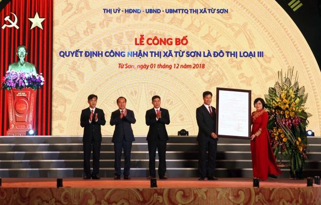 Thứ trưởng Bộ xây dựng Phan Thị Mỹ Linh trao quyết định của Bộ Xây Dựng công nhận thị xã Từ Sơn là đô thị loại III cho lãnh đạo thị xã Từ Sơn