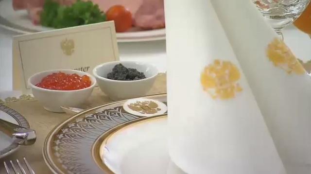 Trứng cá muối đen và cá hồi đỏ, đặt trước đĩa in biểu tượng đại bàng 2 đầu Nga tại bữa sáng của hai nhà lãnh đạo Nga - Đức. (Ảnh: RT)