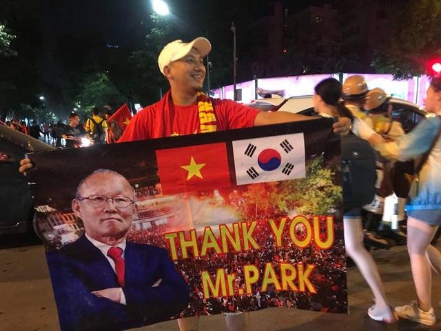 Một cổ động viên đã chuẩn bị banrol có hình ảnh của huấn luyện viên Park Hang Seo giương cao ngoài phố để mừng chiến thắng