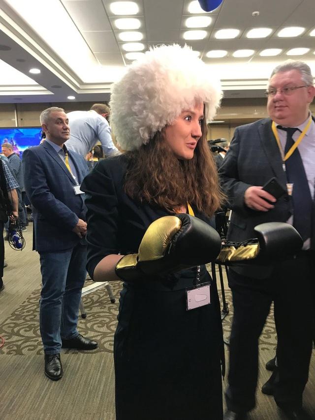 Một nhà báo tới tham gia họp báo với một chiếc mũ lông lớn và một đôi găng tay đấm bốc.
