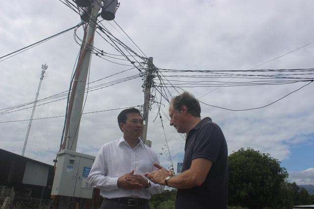 Thứ trưởng Hoàng Quốc Vượng cùng Trưởng phái đoàn EU tại Việt Nam Bruno Angelet trao đổi trong chuyến thăm. Phía sau là hệ thống cột trụ và đường dây điện mới được kéo để hỗ trợ người dân tại huyện Cam Lâm.