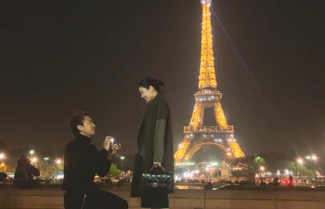 """Trong clip phát tặng cho bạn bè theo dõi về """"hành trình"""" yêu đương của hai người còn có hình ảnh chú rể quỳ gối cầu hôn cô dâu dưới chân tháp Eiffel. Chú rể đã bí mật mua nhẫn và nhờ hai anh chị bạn thân lên kế hoạch rủ nhau ra tháp Eiffel để ăn kem."""