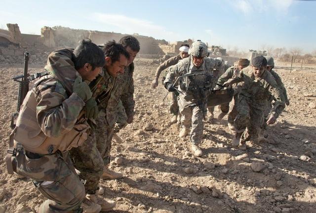 Các binh sĩ Mỹ hỗ trợ cấp cứu các binh sĩ Afghanistan bị thương. (Ảnh: New York Times)