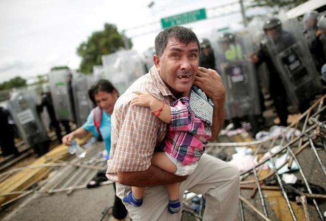 Ông bố Honduras bảo vệ con trong vụ đụng độ giữa đoàn người di cư với lực lượng biên phòng ở Mexico ngày 19/10.