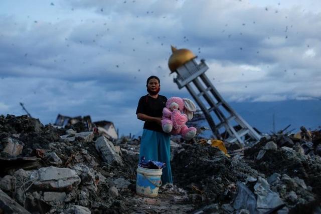Một phụ nữ mất 3 đứa con sau trận động đất tại Palu, Indonesia hồi tháng 10 đứng ở nơi căn nhà của gia đình cô bị phá hủy.