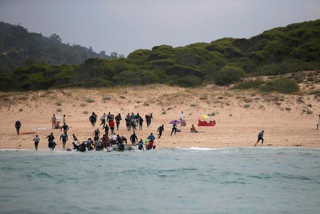 """Người tị nạn ồ ạt chạy từ xuồng lên bờ tại bãi biển ở phía nam Tây Ban Nha sau khi vượt qua eo biển Gibraltar để đến """"miền đất hứa"""" hồi tháng 7."""