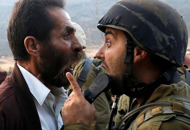 Một người đàn ông Palestine tranh cãi với binh sĩ Israel trong cuộc đụng độ liên quan tới việc Israel ra lệnh đóng cửa một trường học của Palestine gần Nablus, Bờ Tây hôm 15/10.