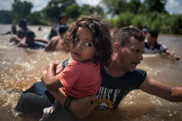 Angel Jesus, bé gái 5 tuổi từ Honduras, được bế qua sông Suchiate khi đoàn người di cư của các nước Trung Mỹ vượt qua Guatemala để vào lãnh thổ Mexico hôm 29/10. Đây là hành trình của đoàn di cư tiến tới biên giới Mỹ.