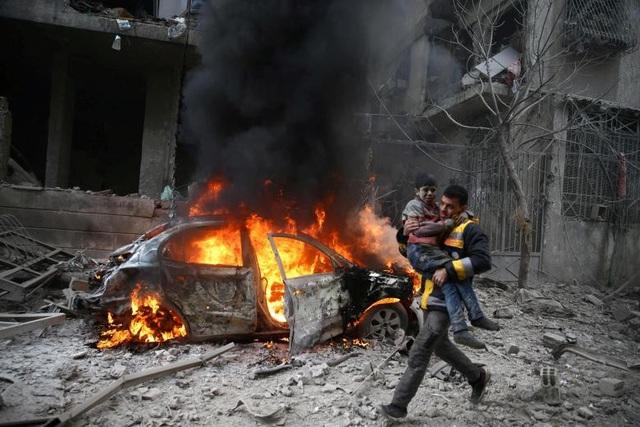 Một thành viên của Lực lượng Phòng vệ Dân sự Syria bế bé trai bị thương khỏi khu vực giao tranh tại thị trấn Hamoria, Đông Ghouta ở thủ đô Damascus, Syria hôm 6/1.