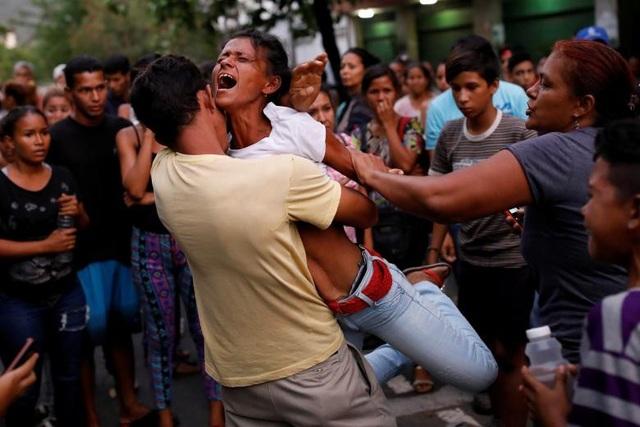 Những người thân của các phạm nhân bị tạm giữ tại sở chỉ huy của cảnh sát Carabobo phản ứng khi chờ bên ngoài nhà tù nơi vừa xảy ra vụ hỏa hoạn ở Valencia, Venezuela ngày 28/3.