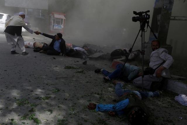 Các nhà báo Afghanistan nằm bất tỉnh trên mặt đất sau vụ đánh bom ở Kabul, Afghanistan hôm 30/4. 9 nhà báo, phóng viên ảnh và quay phim đã thiệt mạng khi đưa tin về vụ đánh bom này.