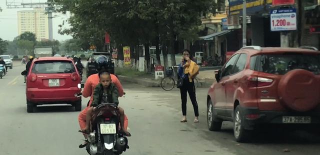 Choáng cảnh bé trai ngồi ngược sau xe máy, oặt ẹo trên phố - 1