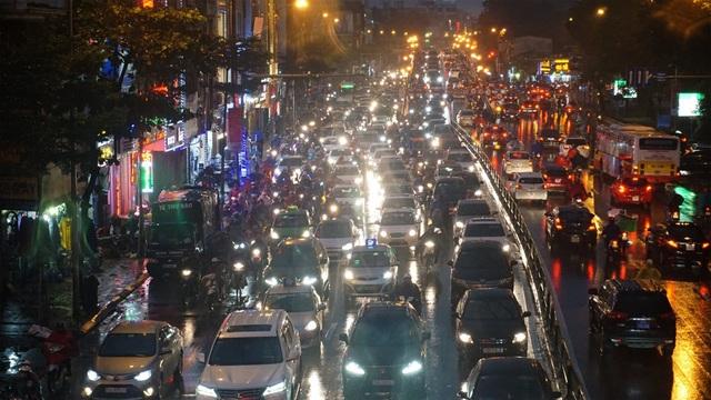 Người dân đổ ra bến xe về nghỉ Tết, đường phố Hà Nội ùn tắc trong mưa - Ảnh 1.