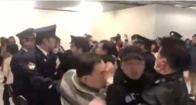 Nhóm khách Trung Quốc xô xát với cảnh sát Nhật Bản trong khi những người đứng sau hát quốc ca (Ảnh: Shanghaist)