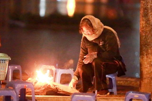 Một người bán nước bên đường đang đốt lửa sưởi ấm ngoài trời gió rét.