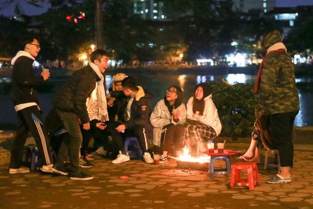 Nhóm bạn trẻ quây quần vui vẻ bên đống lửa nhỏ.