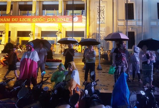Dù trời mưa, nhiều người dân và du khách vẫn theo dõi sự kiện du lịch quan trọng này