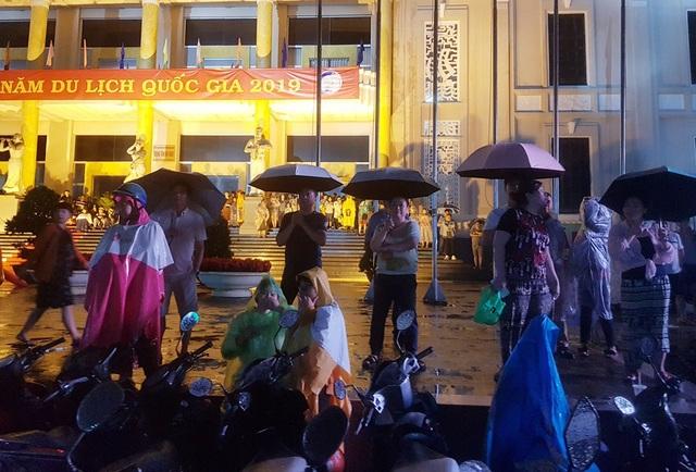 Hàng trăm du khách và người dân che dù, mặc áo mưa theo dõi lễ công bố Năm Du lịch quốc gia 2019 tại TP Nha Trang, tối 31/12 - (Ảnh: Viết Hảo)