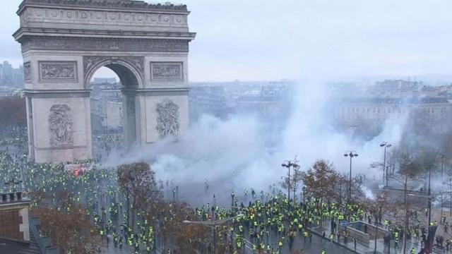 Không khí khá căng thẳng khi người biểu tình chất chướng ngại vật trước Khải Hoàn Môn châm lửa đốt, cũng như xịt bom khói. (Ảnh: Daily Read)