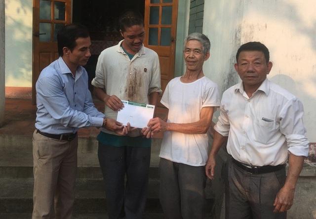 Phóng viên Dân trí và đại diện chính quyền địa phương trao quà bạn đọc ủng hộ tới gia đình ông Cường.