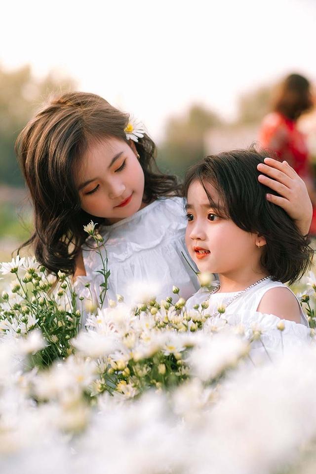 """Bé Thúy Thiện và bé Thanh Tâm ở nhà khá nghịch ngợm và hiếu động. Thế nhưng Thúy Thiện luôn biết cách nhường nhịn và dỗ dành cô em Thanh Tâm. Vẻ trong sáng, ngây thơ của cặp """"thiên thần nhí"""" bên loài hoa cúc họa mi bình dị chính là những hình ảnh đẹp và ý nghĩa."""